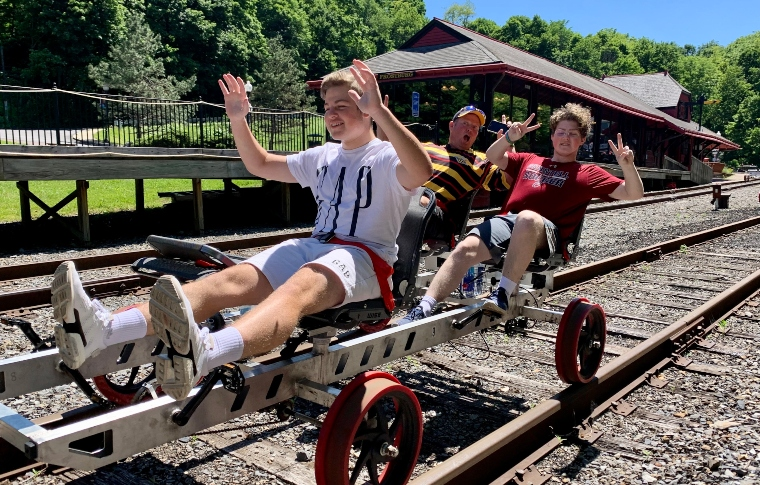 father and two sons posing on a railbike with their hands up